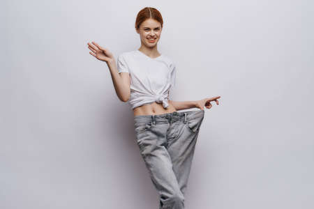 Young beautiful woman on white isolated background, slimming, diet.