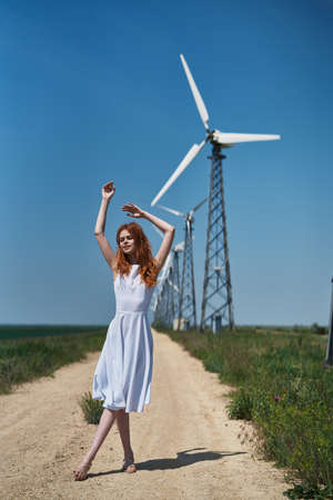 Young beautiful girl on the field on the background of windmills.