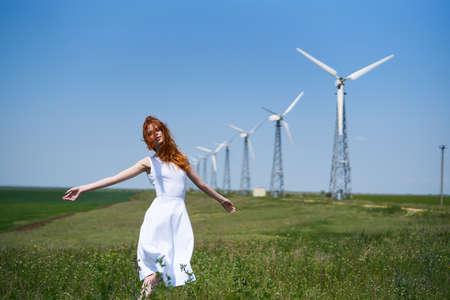 female sexuality: Beautiful young woman in a field against a background of windmills, summer.