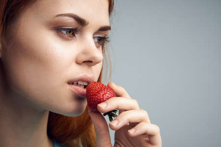 Beautiful young woman on a gray background holds a strawberry. Stock Photo