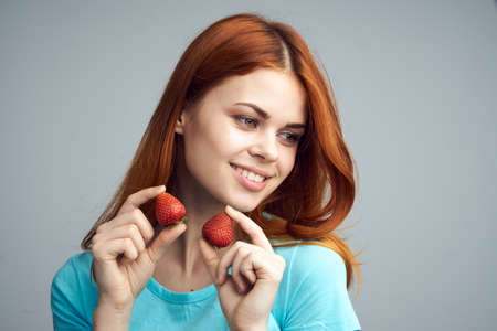 convicts: Beautiful young woman on a gray background holds a strawberry. Stock Photo