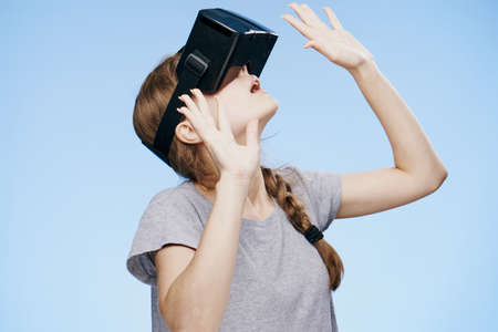 Young woman on a Blue background with virtual reality glasses. Stock Photo