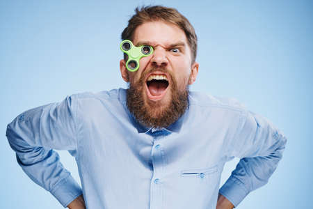 cool gadget: A young guy with a beard on a blue background holds a spinner.