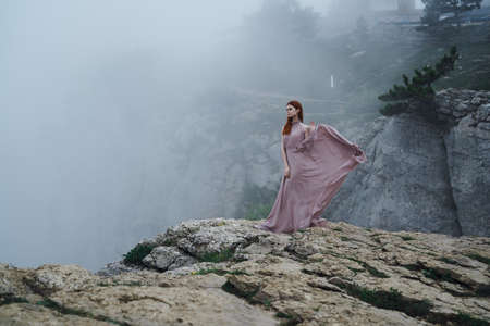 Beautiful young woman in a long dress in the mountains on a cliff.
