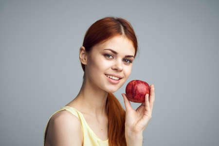 convicts: Beautiful young woman on a gray background holding an apple.