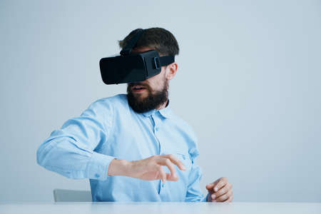 A young guy with a beard on a light background in virtual reality glasses.