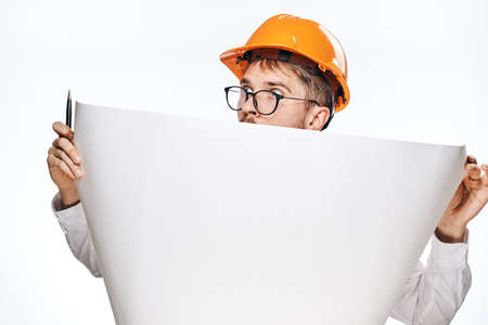 Engineer man with a beard on a white isolated background holds a drawing.
