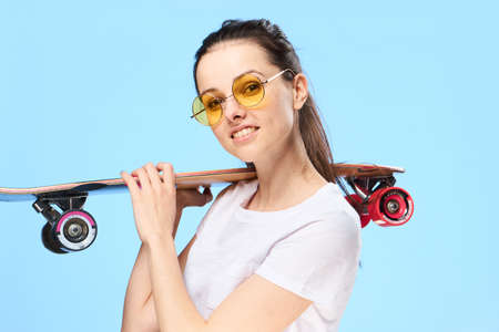 adolescencia: Beautiful young woman on a blue background holds a skateboard.