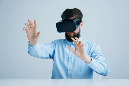 handsfree telephone: A young guy with a beard on a light background in virtual reality glasses.