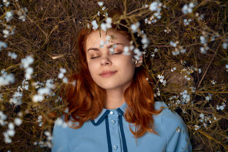 Beautiful young woman lies in flowers in a field.