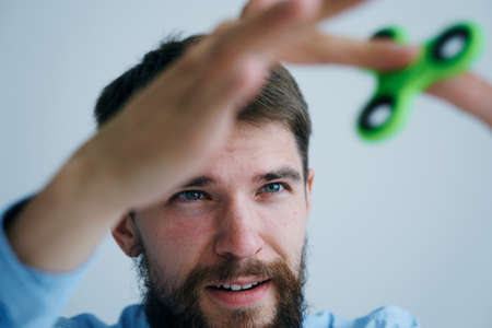 cool gadget: A young guy with a beard on a light background holds a spinner.