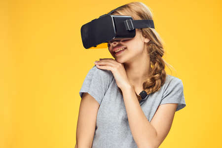 handsfree telephone: Beautiful young woman on a yellow background with virtual reality glasses.