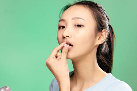 Beautiful young woman on a green background drinking a pill, asian. Banque d'images