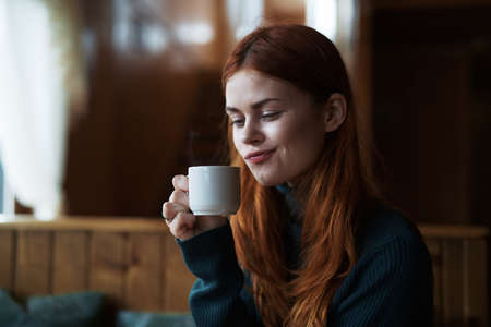Beautiful young woman drinks coffee in a cafe. Stock Photo