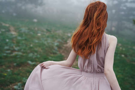 Beautiful young woman in a long dress in the mountains, fog. Stock Photo