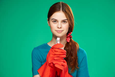 stereotypical housewife: Beautiful young woman on a green background in rubber gloves, cleaning, housework, cleanliness. Stock Photo