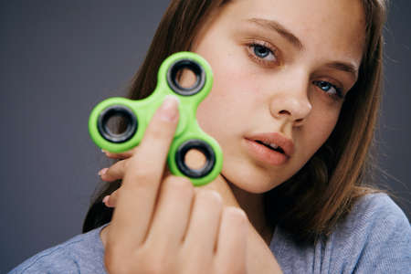 cool gadget: Beautiful young woman on a gray background holds a spinner.