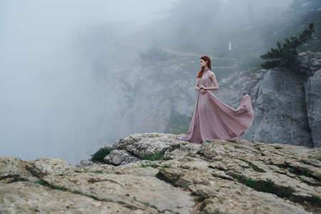 Beautiful young woman in a long dress is standing on a hillside.