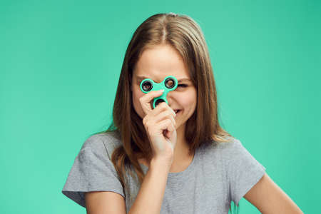 cool gadget: Beautiful young woman on a green background holds a spinner.