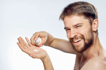 A young guy with a beard on a white isolated background is applying foam for shaving. Stock Photo