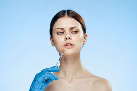 Young beautiful woman on a blue background holds a syringe, medicine, nurse.