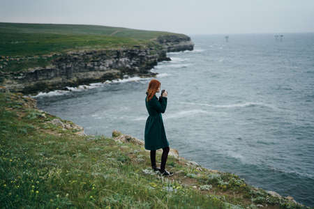 Beautiful young woman standing on a cliff near the sea. Stock Photo