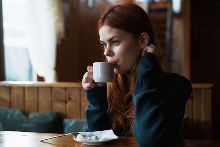 Beautiful young woman is drinking tea in a cafe, the morning.