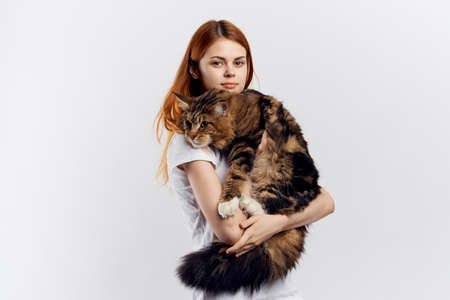 Beautiful young woman on a light background holds a cat.