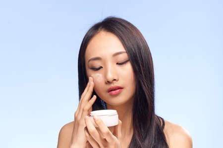 Beautiful young woman on a blue background applies cosmetic face cream, Asian. Stock Photo