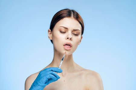 Beautiful young woman on a blue background holds a syringe, medicine, plastic.