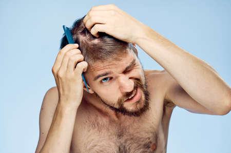 metrosexual: Young guy with a beard on a blue background combing.