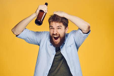 黄色の背景にひげと若い男は、ビール、アルコール、飲酒のボトルを保持します。