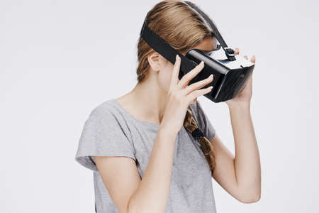 virtual reality simulator: Beautiful young woman on white isolated background in virtual reality glasses. Stock Photo