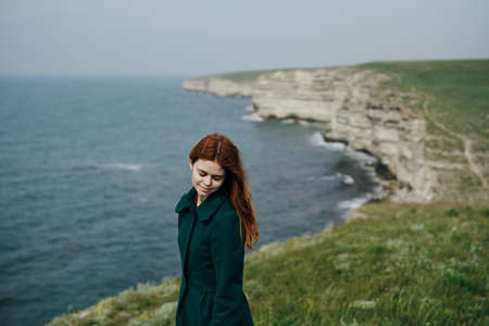 Beautiful young woman on a cliff of a mountain near the sea. Stock Photo