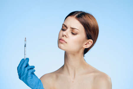 Beautiful young woman on a blue background holds a syringe, plastic, medicine. Stock Photo