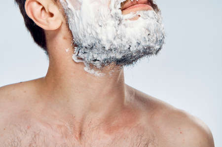 Young guy with beard on white isolated background in foam for shaving.