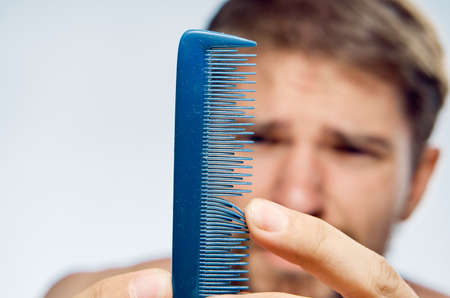 Young guy with a beard on a white isolated background holds a comb.