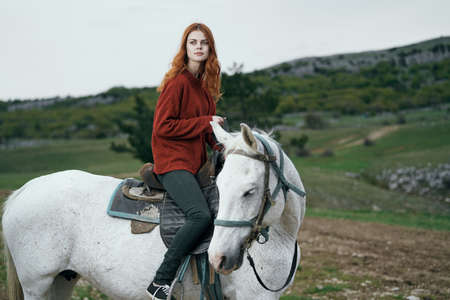 Beautiful young woman walking in the mountains with a horse. Stock Photo
