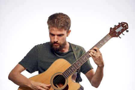 plucking: Young guy with a beard on a light background playing the guitar. Stock Photo