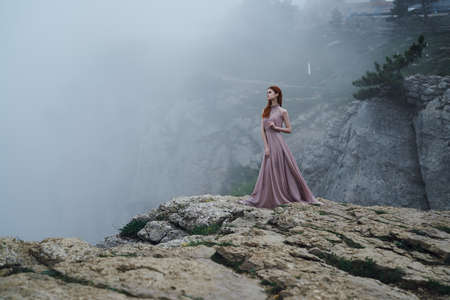 Beautiful young woman in a long pink dress is standing on a hillside.
