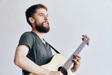 plucking: Young guy with a beard on a white isolated background holds a guitar.