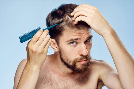 metrosexual: Young guy with a beard on a blue background holds a comb.