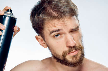 Young guy with a beard on a white isolated background does a hairstyle.
