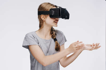 Beautiful young woman on white isolated background in virtual reality glasses. Stock Photo