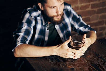 A young guy with a beard drinks beer in a bar.
