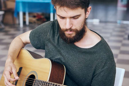 plucking: Young guy with a beard playing the guitar.