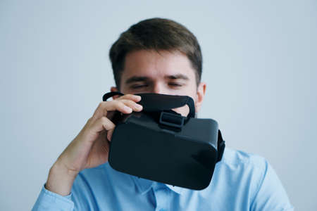 A young guy with a beard on a light background holds virtual reality glasses.