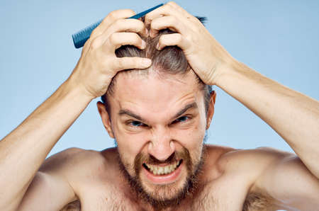 barber: Young guy with a beard on a blue background holds his head.