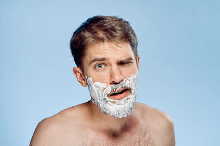 Young guy with a beard on a blue background in shaving foam.