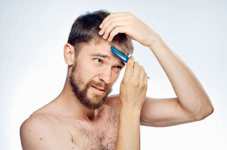 metrosexual: Young guy with a beard on a light background combs his hair.